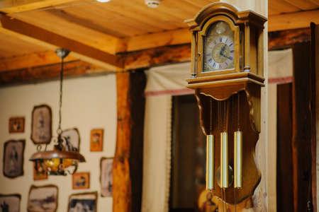 Antiquarian wooden clock with a pendulum in a retro interior