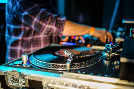 Close up of dj control panel playing party music on modern player in disco club. Nightlife and entertainment concept. Defocused background with shallow depth of field and focus on buttons near mixing hand. Spinning, Mixing, and Scratching in a Night Club