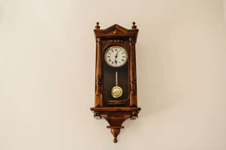 Antique wall clock with a pendulum from wood isolated on a white background Foto de archivo