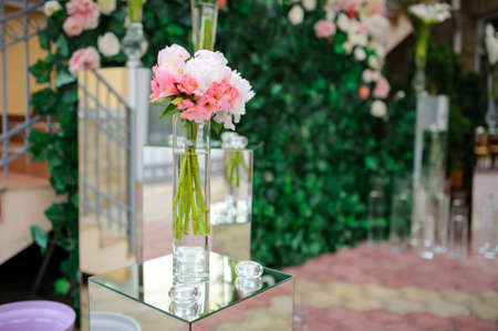 Flowers decoration background for wedding party. Composition from alstroemeria, roses and ranunculus in mirror vase