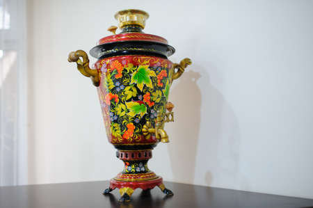 Samovar painted with leaves, flowers and berries on a wooden table against the background of a white wall