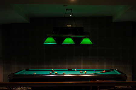 The pool table up lighted, with green lusters, close view