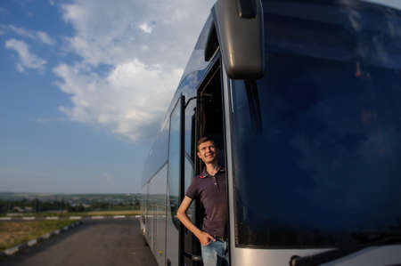 Young handsome man is looking from the bus doorand wering a t-shirt and smiling