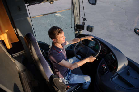 Young handsome man at the wheel is looking away from the bus, top view, wering a t-shirt and smiling.