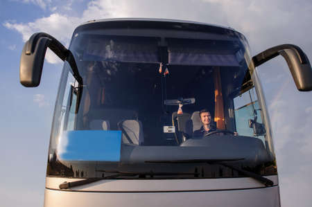 Young handsome man at the wheel in the silver bus is looking away , top view, wering a t-shirt and smiling.