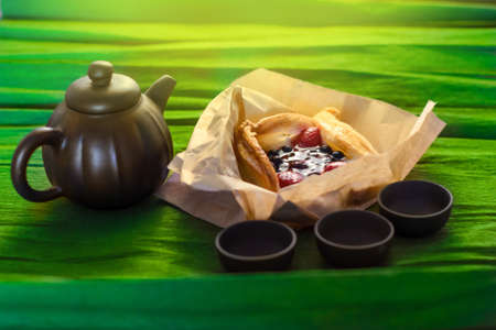 Three cups, a kettle of ceramics and a cake on the green background, close view