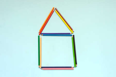 A house maden with colored pencils, blue background, top view