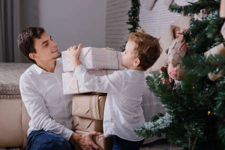 Father and son with presents near a Christmas tree