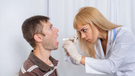 The doctor is looking in the mouth of the patient, close view