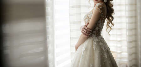 The bride in ivory dress at the window, close view Imagens - 142514506