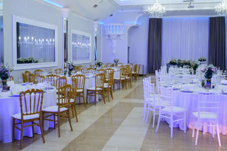 The interior of a wedding banquet hall: round tables with white tablecloth and all necessary supplies for dinner on them, bouquet of flowers; gray curtains, beige floor, white walls and ceiling, white and brown chairs Foto de archivo