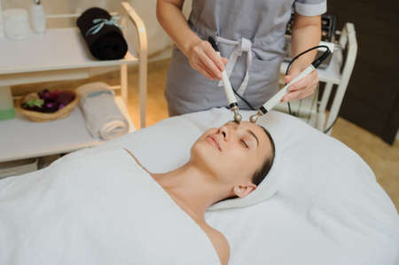 Lateral view of woman facial massage spa procedure. Electric stimulation facial skin care. Microcurrent lift face. Beauty spa procedure. Anti aging rejuvenation non surgical treatment in medical interior room
