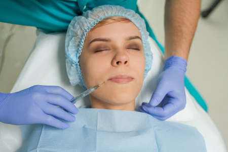 Top view of lips augmentation procedure on a young woman done by a cosmetologist doctor with Hyaluronic acid Injection.