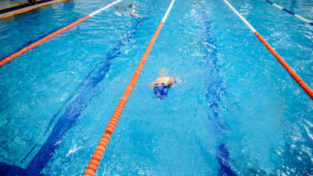 a 6-year boy swims backstroke in a swimming pool for competition Zdjęcie Seryjne