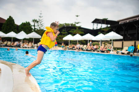 a 6-year blond boy in a life vest jumping in the swimming pool of a hotel in Turkey Foto de archivo