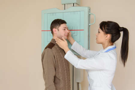 Female doctor preparing the patient for paranasal sinuses or nasal bones x-ray/radiography procedure in the radiologist's cabinet