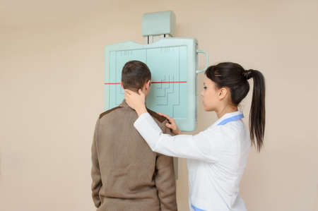 Female doctor preparing the patient for paranasal sinuses x-ray procedure in the radiologist's cabinet
