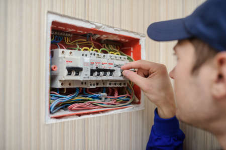 lateral view of a young eletrician in blue overall disassembling a electrical panel with fuses in a house