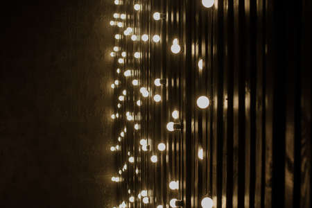 close up photo of golden light bulbs in vertical lines along a wall in the dark