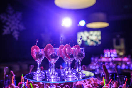 Buffet table with snacks, canapes; shrimp with sauce in glasses at a birthday party in blue lights