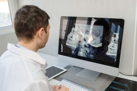 lateral view of a male radiologist examining neck x-rays (cervical vertebrae) on computer Foto de archivo