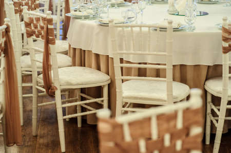 close up photo of white chairs decorated with brown textil in a banquet hall in white and brown colors decorated for the event Stock Photo
