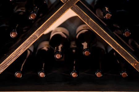 close up photo of wine bottles stacked on wooden racks in cellar