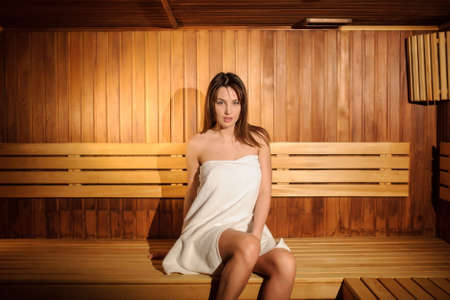 close up photo of a beautiful woman wearing a white towel in a wooden sauna