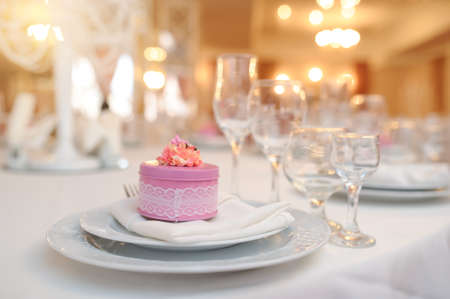 close up photo of knife and fork in a folded napkin on two plate near a set of glasses and a pink round gift box with a flower on the top on the napkin