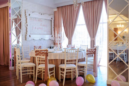 close up photo of a table in a banquet hall in white and brown colors decorated for the event