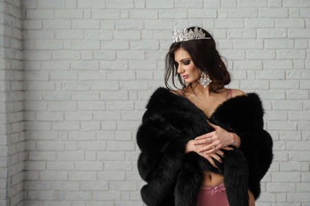 close up photo of a fashion woman in black fur coat and pink underwear with a crown on her head on white brick background