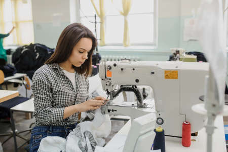 close up photo of a young woman sewing with sewing machine in a factory
