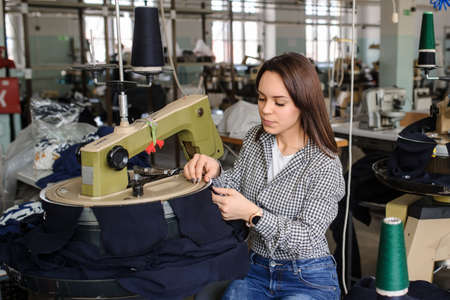 close up photo of a young woman working with linking machine for knitting in textile industry 版權商用圖片