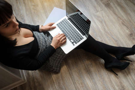 lateral view of a hot brunete in office outfit sitting on the floor and working on computer