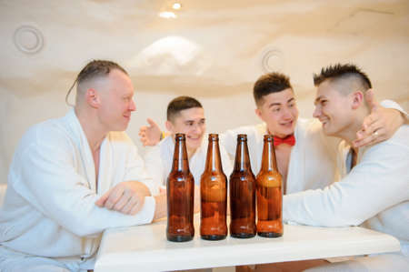 close up photo of 4 men in white gowns sitting around a table and drinking beer after sauna procedures