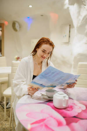 close up photo of a beautiful reddish woman in white bath gown looking in the menu in the fito bar of a spa centre