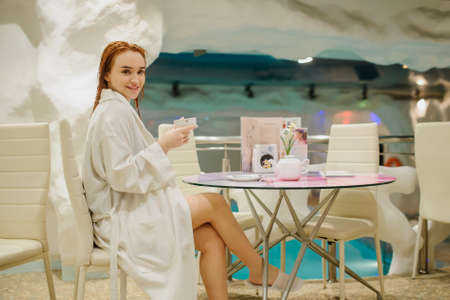 close up photo of a beautiful reddish woman in white bath gown drinking tea in the fito bar of a spa centre