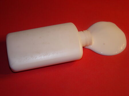 Plain white bottle of glue with no lid pouring onto red paper photo