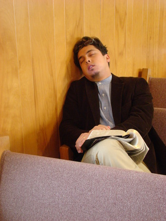 Man sitting up sleeping in church Stock Photo