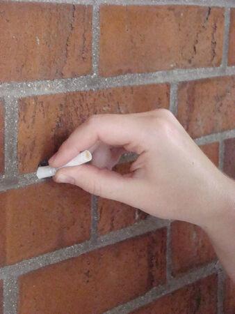 extinguishing: Extinguishing cigarette on brick wall