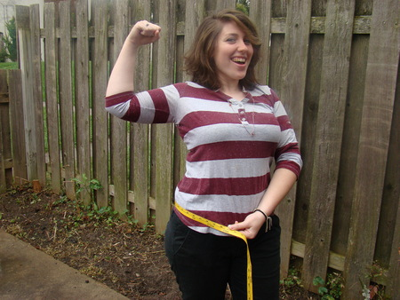Happy young woman with tape measure around her waist has lost weight