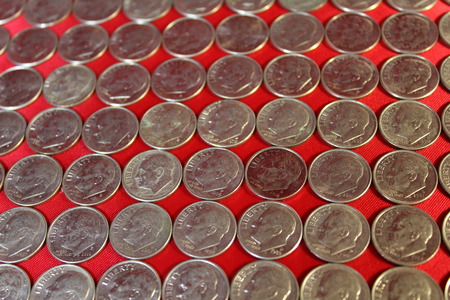 e pluribus unum: Many dimes with a red background Stock Photo