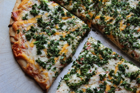 adulation: Freshly made and sliced kale pizza