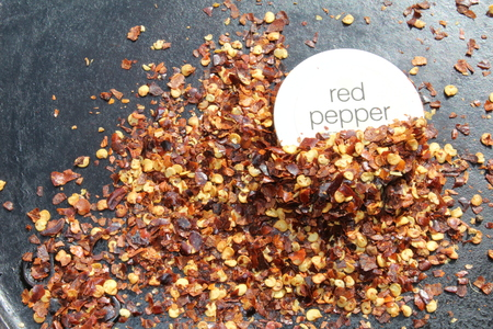 pepper flakes: Red Pepper flakes around a labeled lid