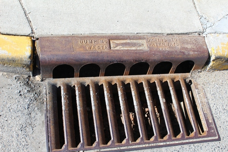 Old metal urban street corner storm drain with a fish on it