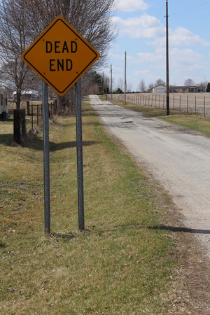 end of a long day: Dead end sign on a long straight country road on a beautiful sunny day