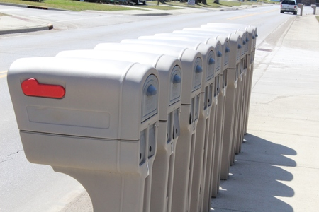 Several Identical plastic mailboxes in a row at the edge of a street Stock Photo