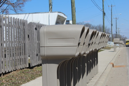 the u s  flag: Several Identical plastic mailboxes in a row at the edge of a street Stock Photo