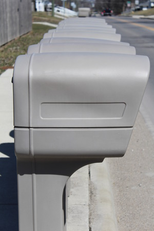 Identical grey mailboxes in a row Stock Photo