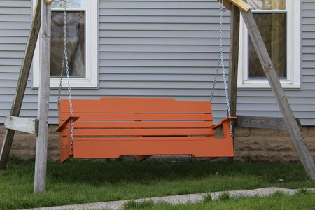 Attractive orange family swing sitting on the lawn